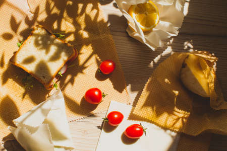 Set of healthy snack packed into sustainable beeswax cloth. Zero waste concept of product storage. Fresh cherry tomatoes, bread, lemon, sandwich wrapped into beeswax cloths. Reklamní fotografie