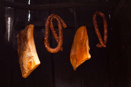 Smoked sausages meat and lard hanging in smokehouse.