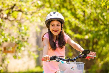 Smiling girl in helmet ride on the pink girly bike