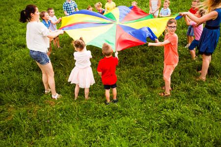 Close view children holding large colorful parachute Reklamní fotografie