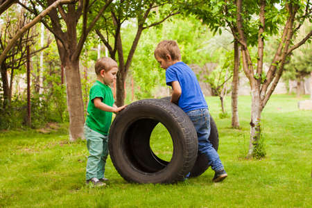 The little boys are interested in car tires 写真素材