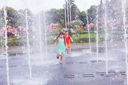 The cute kids escape from the heat in a city fountain