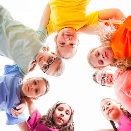 Circle of smiling kids embracing together in t-shirts