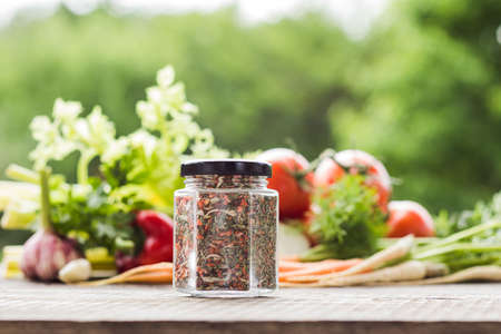 Glass jar filled with seasoning, bunch of fresh vegetables on background, blured