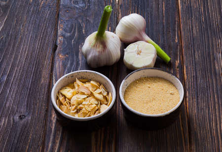 Fresh, dried and ground garlic on wooden surface Standard-Bild