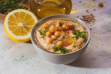 Bowl of hummus with chick peas and greenery on top