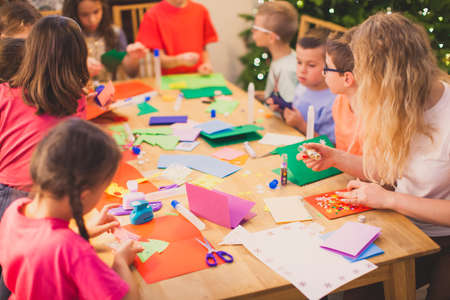 Teacher with her children while Christmas cards workshop