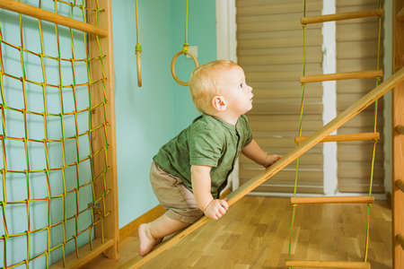 Comprehensive physical development in the gym for a toddler boy Stockfoto