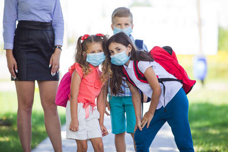 Group of elementary school students wearing face protective medical masks