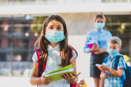 Schoolgirl in medical mask looking at the camera