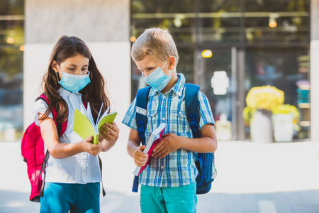 Kids in protective masks outdoors looking at their copybooks Stockfoto