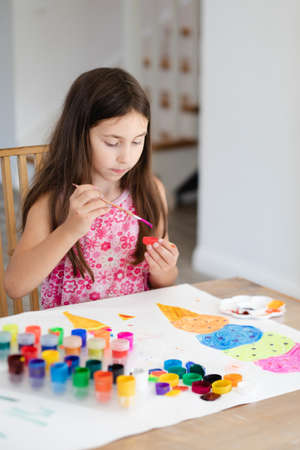 Lovely girl concentrates on her painting at home