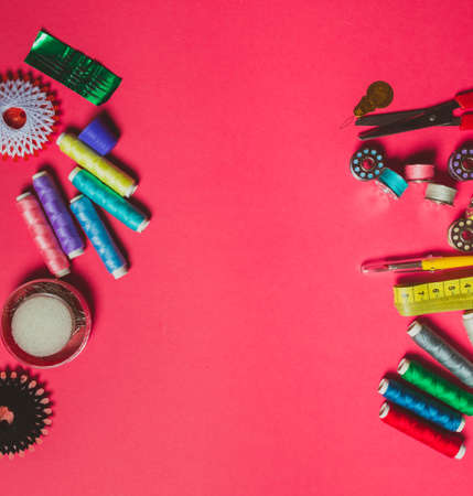 Colorful threads and spools on bright pink background Stockfoto