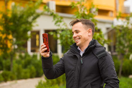 The happy man is holding phone and having video chat outdoors