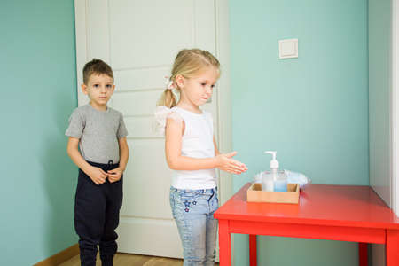 The little kids disinfect their hands in the class