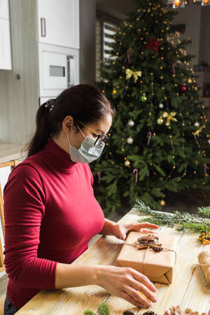 Young adult woman in medicine mask is packing gifts