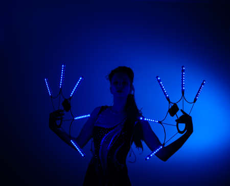 Woman in blue light dancing while light show