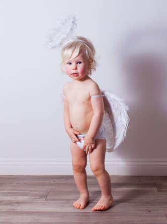 the baby with angel wings and nimbus indoors