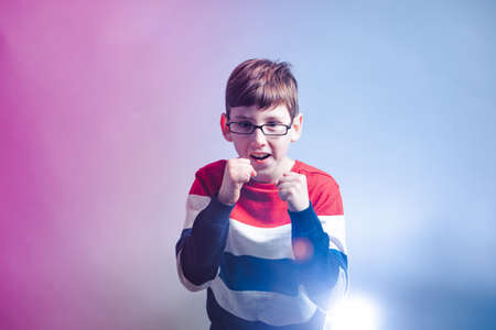 Portrait of young boy in warior pose holding fists