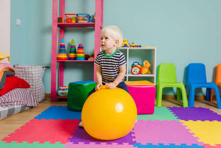 Cute blond boy trying to jump on the yellow fitball