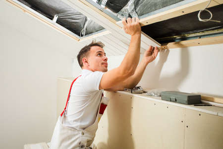 the builder fastens wooden boards in the attic
