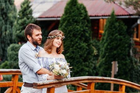 Eclectic rustic wedding couple stand on the bridge