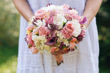 Stylish romantic wedding bouquet in the bride hands