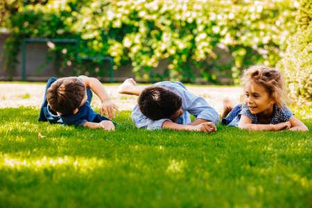 Portrait of three little children lying on a green grass