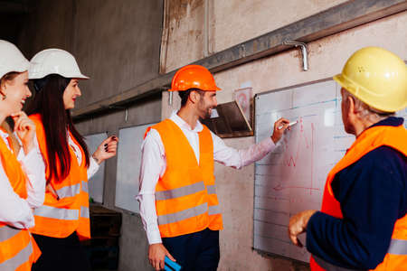 The young engineers are practicing at the factory Фото со стока
