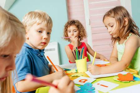 Preschool children learn english alphabet using cards Foto de archivo