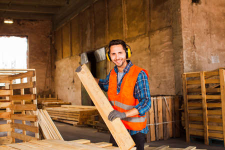 The young worker in uniform works at the warehouse