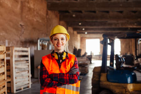 The woman woodworker chooses a board in a warehouse