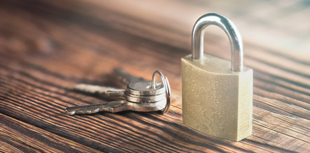 estate concept with symbol of security, lock padlock with key on old wooden background.