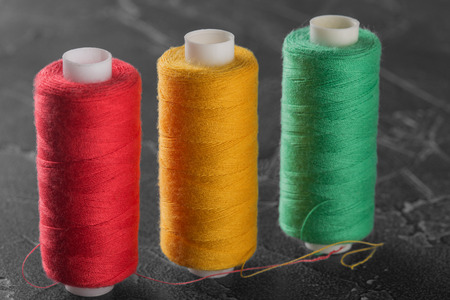 sewing thread of different colors yellow red green Stock Photo