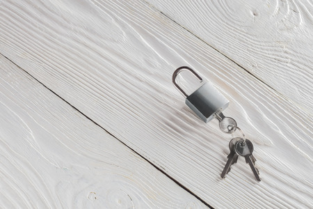 estate concept with symbol of security, lock padlock with key on wooden background.