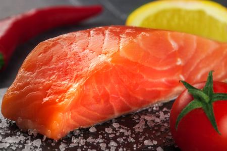 trout with lemon  and tomato on black stone Stockfoto - 116143056