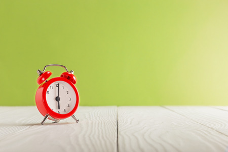 Clock on light wooden table with colorful background. Time for wake up. Banco de Imagens