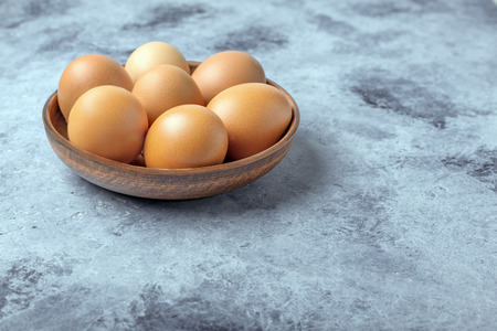 Chicken eggs in a ceramic bowl on the table. Useful product - a lot of calcium and protein.