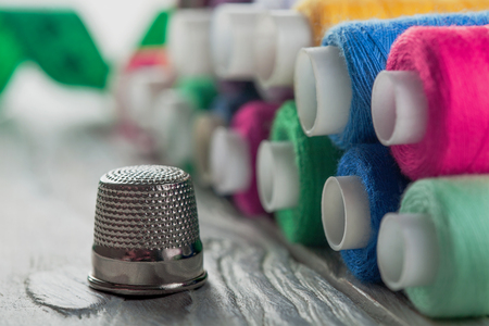 colored sewing thread and bobbin on a wooden background