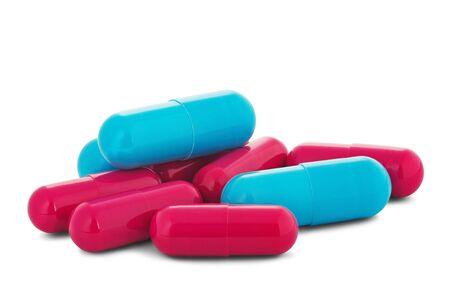 Stapel von medizinischen Pillen in den roten und blauen Farben auf weißem lokalisiertem Hintergrund mit Schatten.