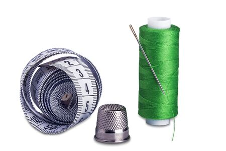Spools with needle, thimble and measuring tape..Safety and caution while sewing. Stockfoto