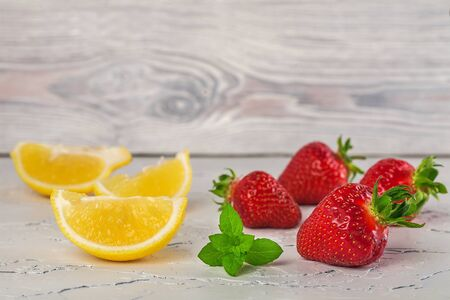 strawberries with lemon and mint on a white stone Banco de Imagens