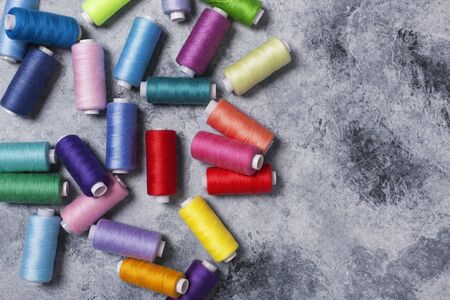 Colorful threads on bobbins, sewing set.On gray concrete background. Place for text.