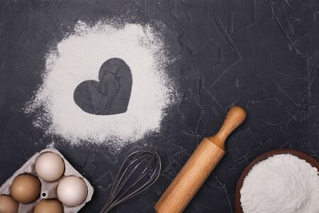 Eggs, flour and rolling pin on a dark background. Free space for text.