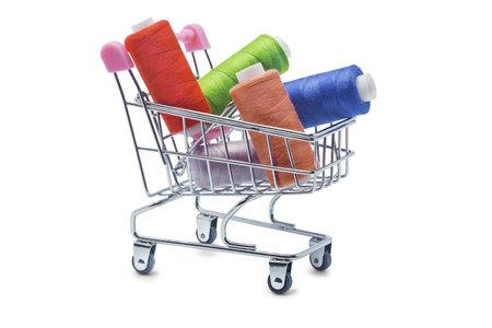 Shopping basket on wheels. Sewing threads on bobbins.