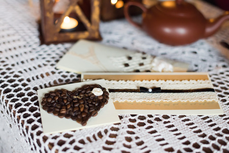 Postcard with coffee beans in the shape of a heart is on the white tablecloth Stock Photo