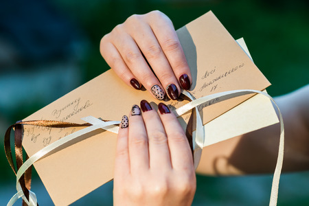 letter writing: Beautiful hand of a young woman with brown manicure holding an mail envelope isolated