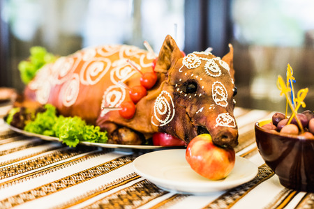pig roast: Decorated and roast suckling pig with an apple in his mouth on a white plate on banquet Stock Photo