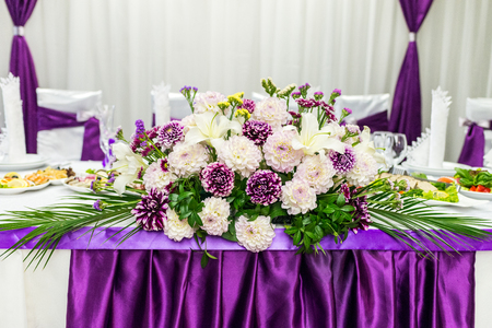 beautifu: food table decorated with purple and white beautifu flowers for wedding Stock Photo