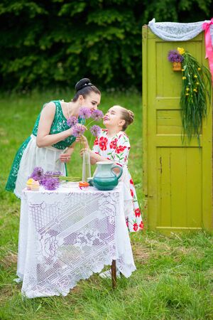 Young mother and her daughter cooking cupcakes together in the backyard